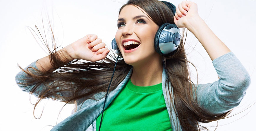 Young women dances to music while wearing headphones | Featured image for Relaxing after work.