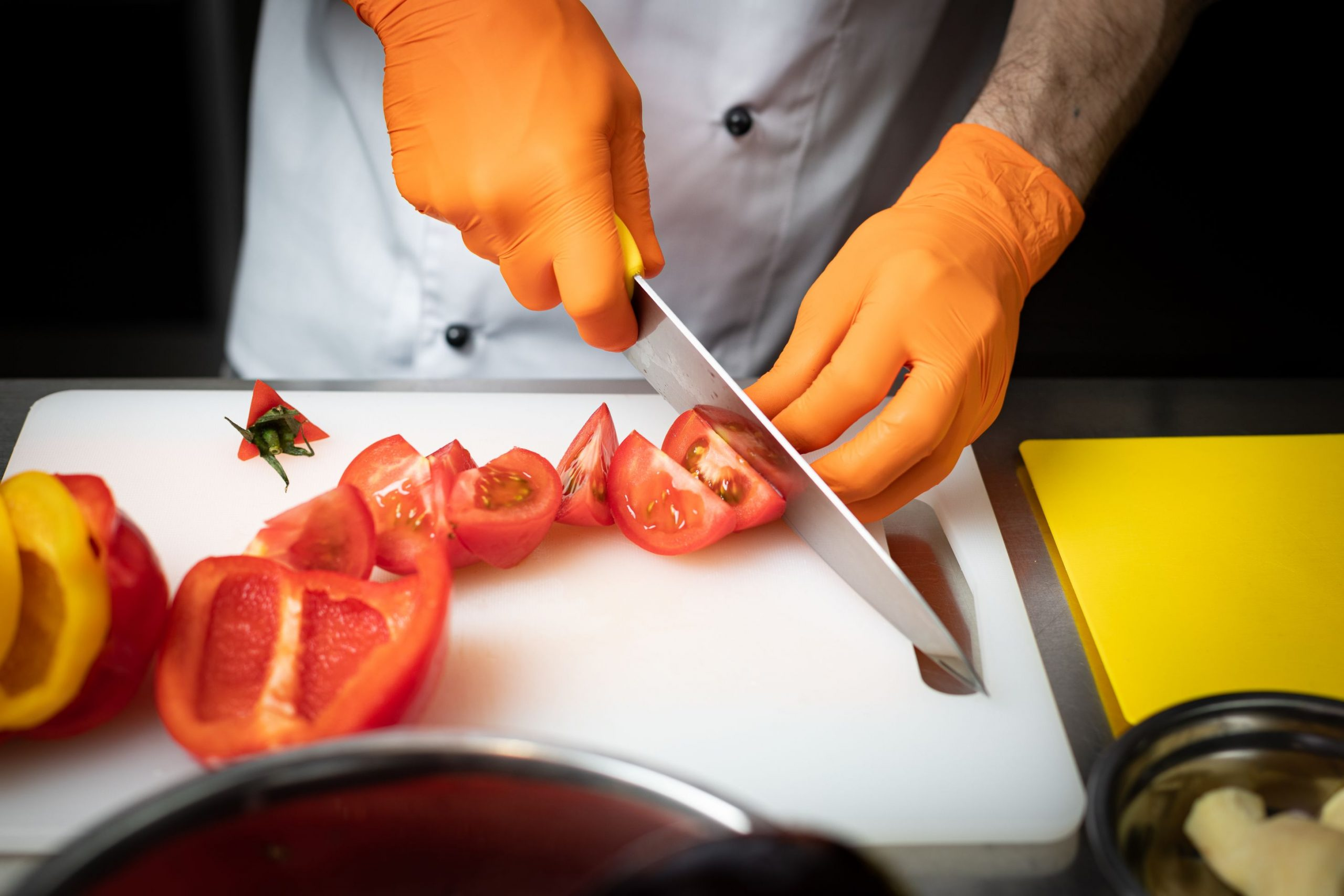 Chef cuts tomatoes | Features image for HLTSS ICFH66 FOR FOOD HANDLING.