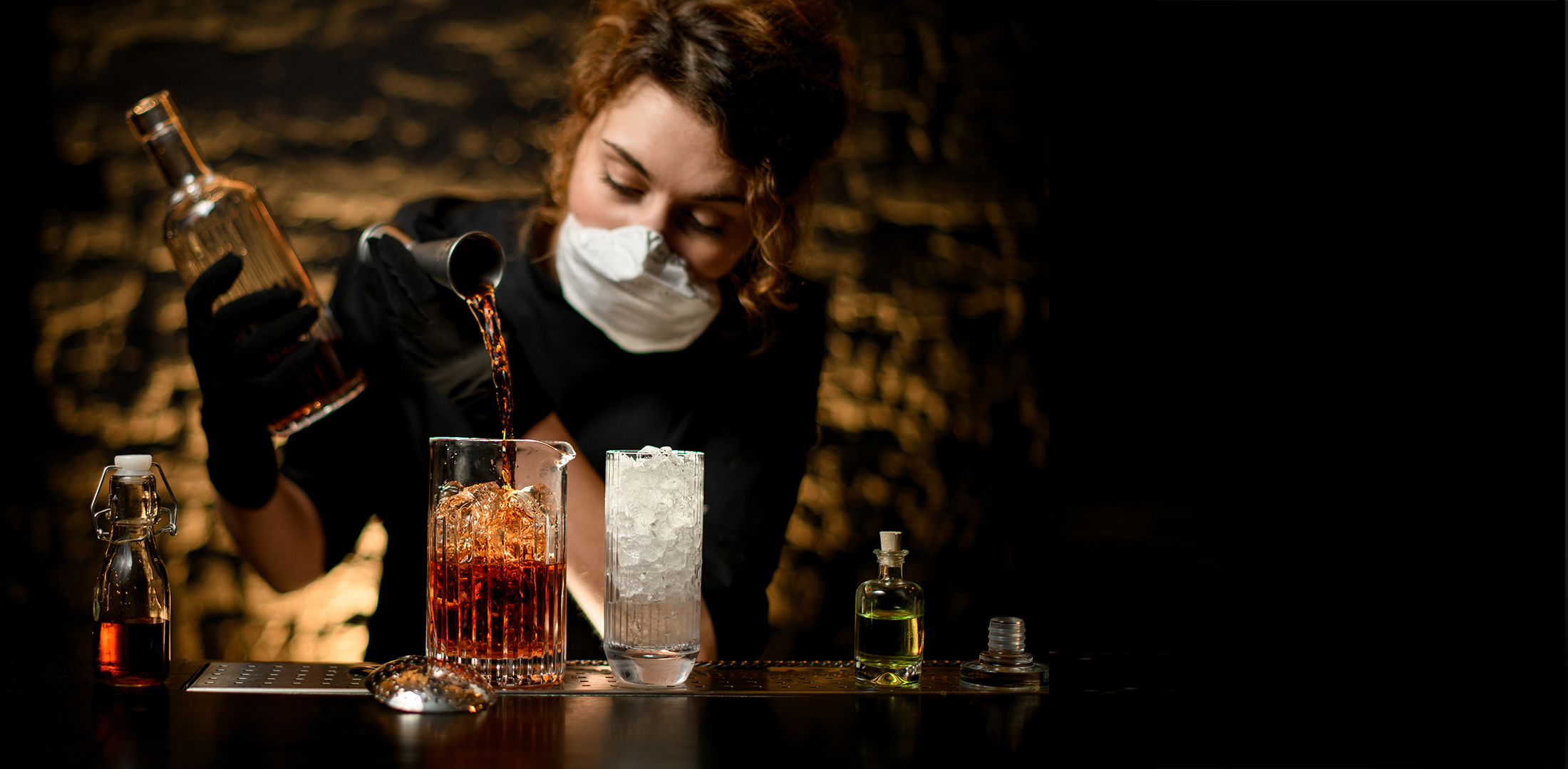 Woman bartender in black clothes pours cocktail | Featured image for HLTSS ICHS64 FOR HOSPITALITY.