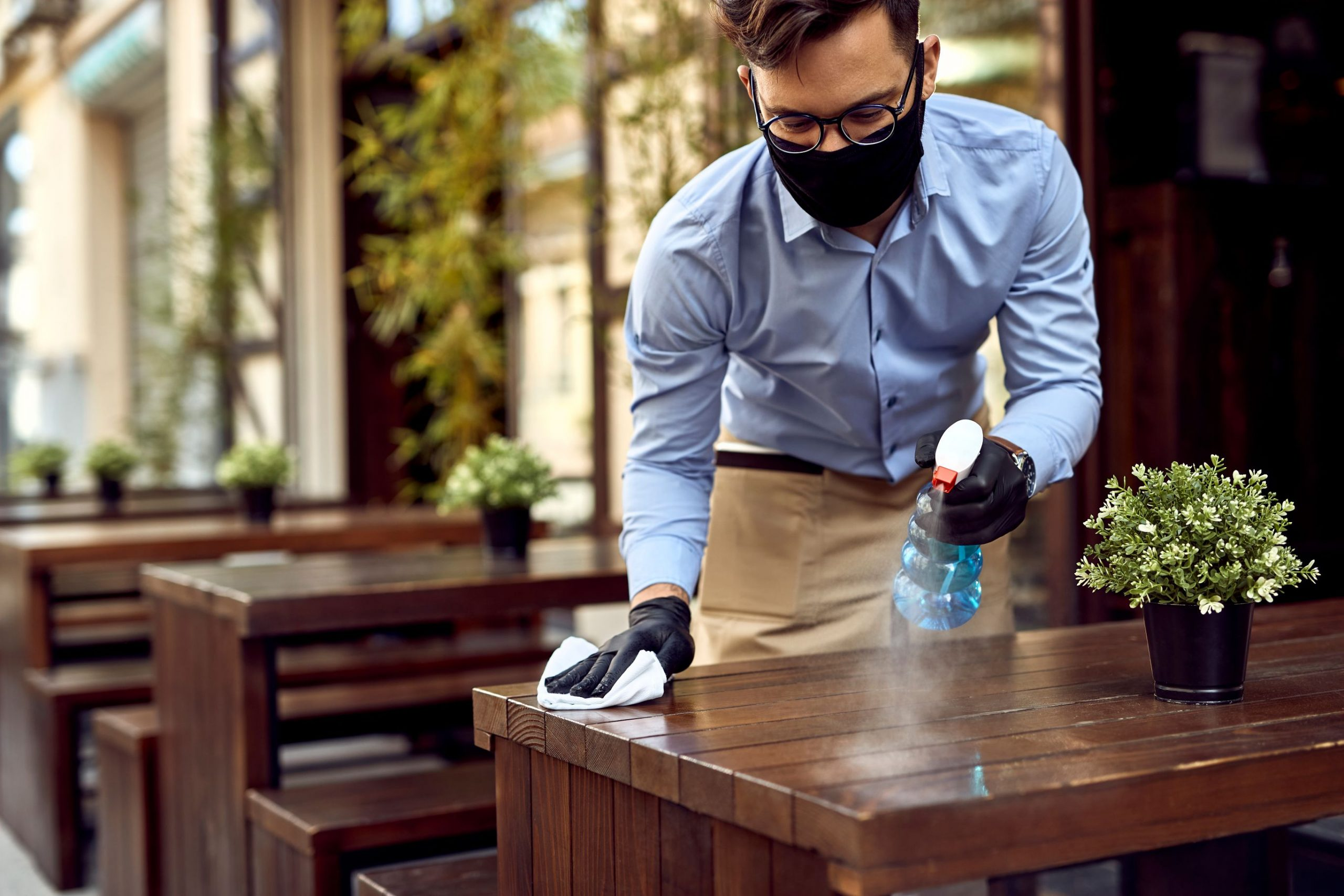 Waiter disinfecting table during COVID-19 | Featured image for HLTSS ICHS64 FOR HOSPITALITY.