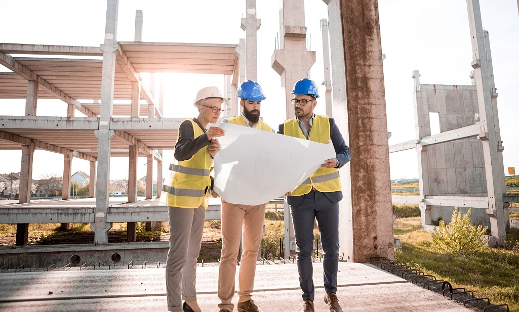Builders review building plans in front of construction site | Featured image for How to get your Builders License.