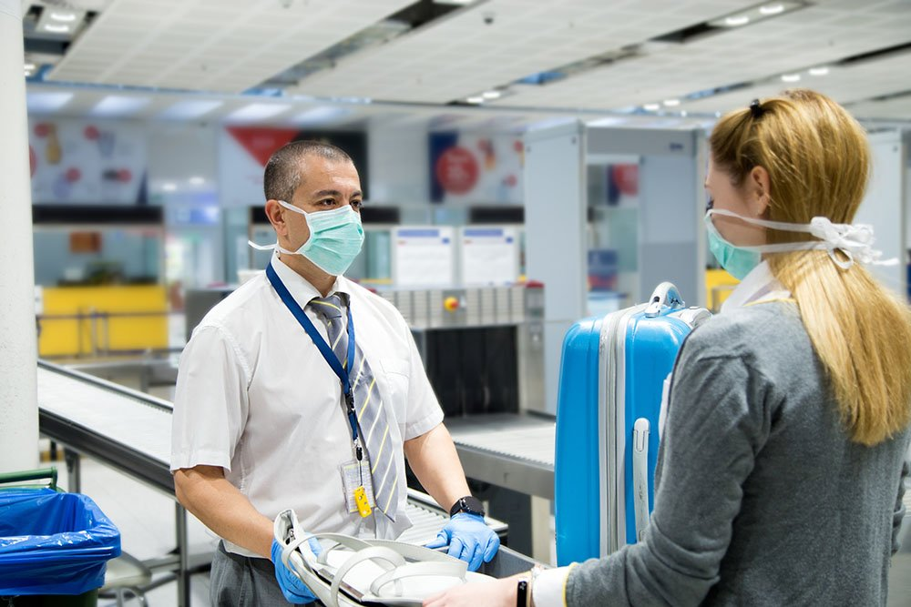 Security officer at airport scans luggage during COVID-19 | Featured image for INFECTION CONTROL TRAINING ACT - SKILL SETS.