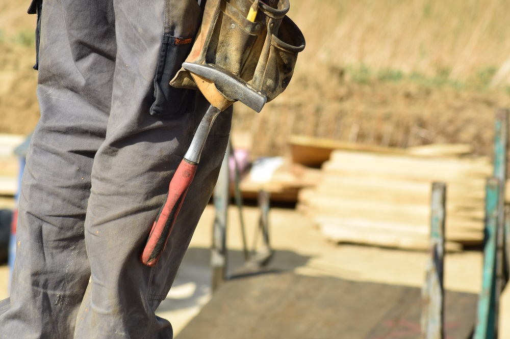 Builder shows construction hammer | Featured image for How to get your Builders License.