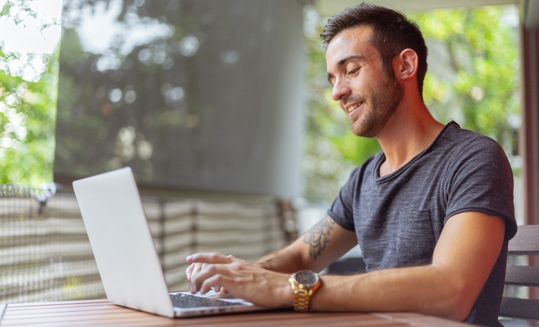Happy looking man types on a laptop wearing a gold watch | Featured image for Virtual Classrooms.