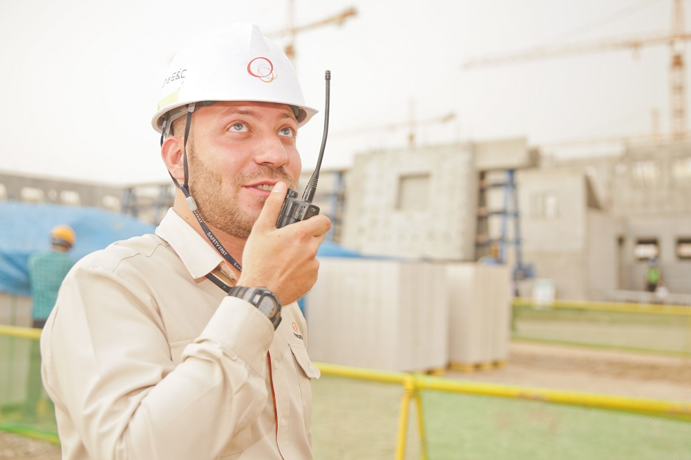 Man talks on a walkie-talkie | Featured image for How to get your Builders License.