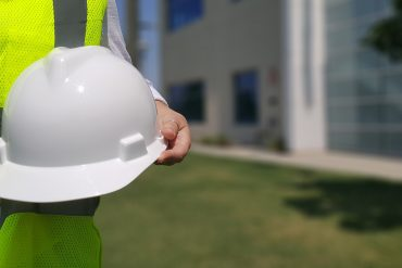 Person in hi-vis jacket holding white hard hat | Featured image for short construction courses.