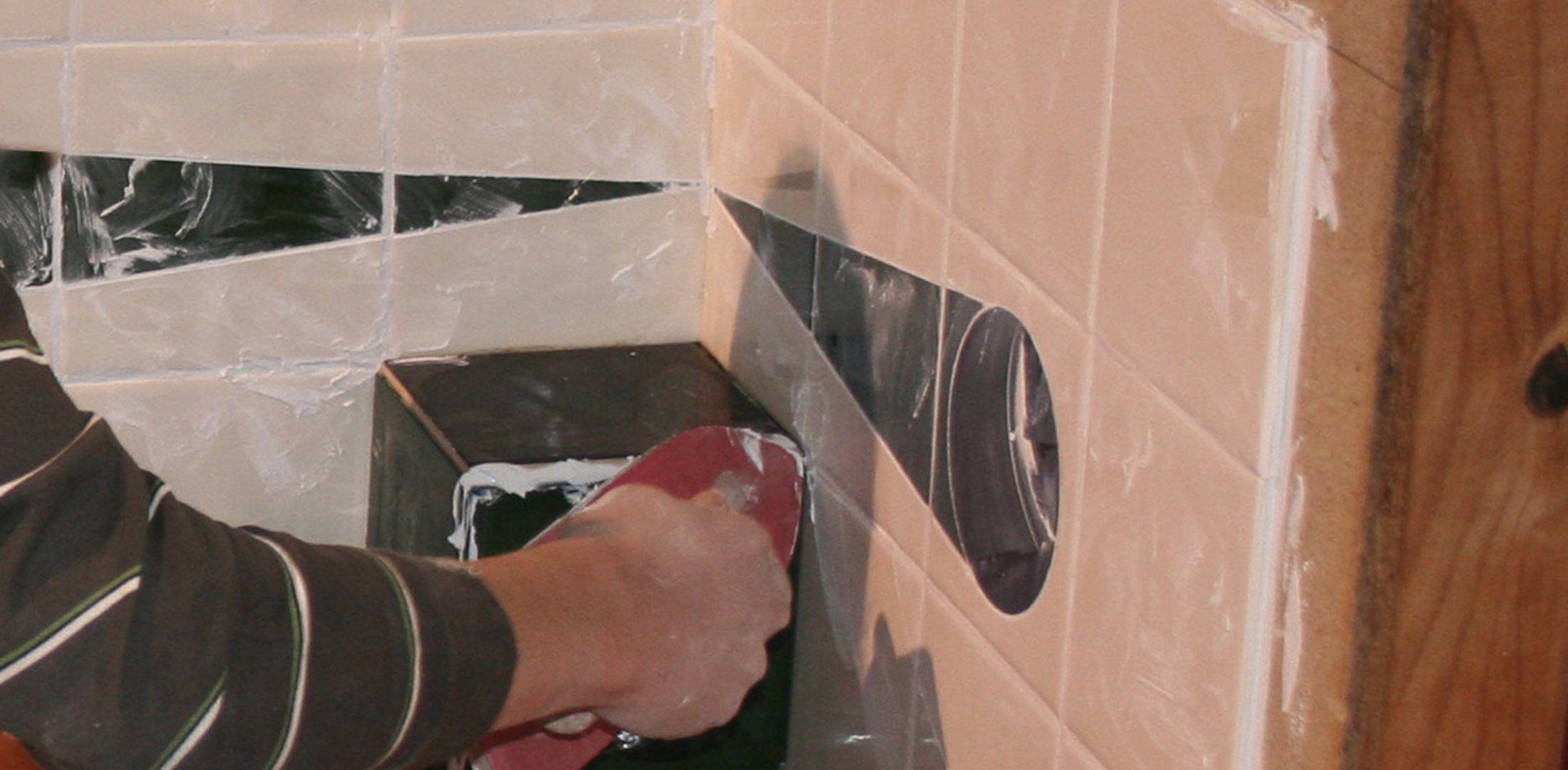 Image of tilers applying grout at training school | Featured image for Courses in Building and Construction.