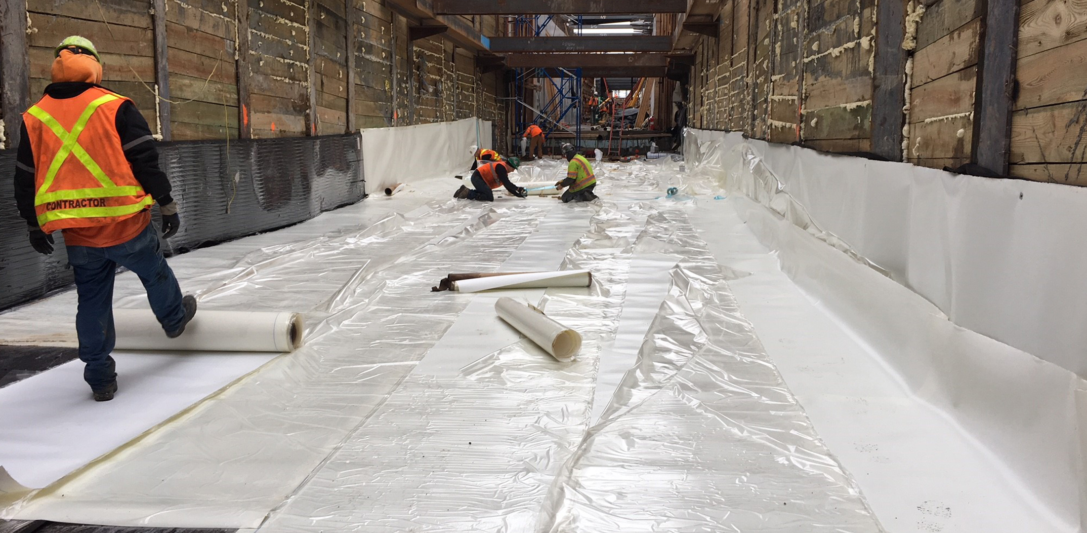 Image of construction workers laying waterproof sheets | Featured image for Courses in Building and Construction.