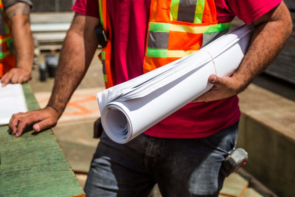 A construction worker bringing drafting paper to a meeting