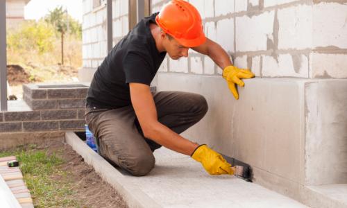 Construction worker waterproofing a building