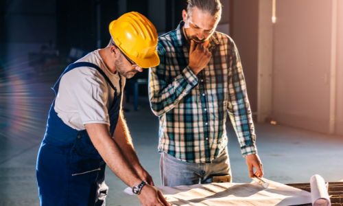 Two men reviewing construction and building plans