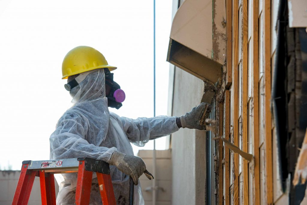 A professional removes possible asbestos-containing materials